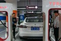 People charge their Tesla vehicles at a charging station inside a mall in Shanghai. Photo: AFP