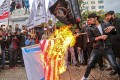 Palestinian protesters burn the US and Israeli flags in Gaza City with President Donald Trump set to recognise Jerusalem as Israel's capital. Photo: AFP