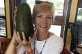 Pamela Wang poses for a photo in Kealakekua, Hawaii, with a huge avocado she found while on a walk. Photo: AP