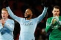Manchester City's Raheem Sterling (centre), Kevin De Bruyne (left) and Ederson celebrate with their fans after defeating Manchester United. Photo: Reuters