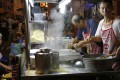 A cook prepares a noodle dish from a street food stall along Lebuh Chulia, a popular nightlife strip, in George Town on the island of Penang, Malaysia. Photo: AP Photo/Adam Schreck
