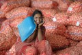 Indian labourers speaks on a cellular telephone as she sits on onion bags at a wholesale market yard in Hyderabad on August 17, 2013. Photo: AFP