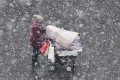 A woman pushes a baby carriage through heavy snow in Yantai in Shandong province earlier this month. The rush to convert from coal heating systems to gas has led to shortages of the fuel in China's north. Photo: Agence France-Presse
