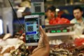A customer scans an Alipay QR code to make a payment via a mobile phone in a market in Beijing. Photo: EPA