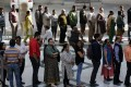 Voters wait in a long queue to cast their votes at a polling station during the second phase of Assembly election of Gujarat state. Photo: EPA