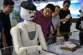 People watch a robot painting demonstration during the 19th China Hi-tech Fair in Shenzhen, south China's Guangdong Province. Photo: Xinhua/Mao Siqian