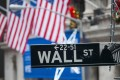 A Wall Street sign is seen in front of the New York Stock Exchange (NYSE) in New York. Stocks hit fresh highs as the vote on US tax legislation looms. Photo: Bloomberg