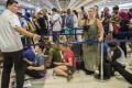 Passengers wait in line at a ticketing counter at Ngurah Rai International Airport near Denpasar, Bali, Indonesia. Weeks ago tourists were stranded by disruptions from the Bali volcano. Photo: Reuters