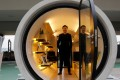 "Architect James Law poses earlier this month inside his work, the ""Opod"" – a 120-square foot giant water pipe, designed as micro-housing in Hong Kong. Photo: Reuters"