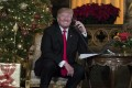 President Donald Trump's commission into voter fraud will be allowed to request detail of voters, a Washington appeal court has declared. Pictured: Trump smiles to the media as he speaks on the phone with children on Christmas Eve. Photo: AP/Carolyn Kaster)