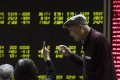 Investors look at screens showing stock market movements at a securities company in Beijing. Experts say China's elderly can be particularly vulnerable to risky or even fraudulent investments, such as P2P online lending. Photo: AFP