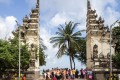 Chinese tourists at the entrance to Kuta Beach in Bali. Photo: Alamy