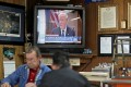 A newscast showing President Donald Trump plays on an old television set as customers play cards in the Frosty Freeze restaurant in Sandy Hook, Kentucky. For supporters of Trump, their faith in him remains unshaken. Photo: AP