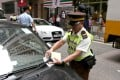 A traffic warden issues a ticket for illegal parking in Tsat Tsz Mui Road in North Point. Photo: Sam Tsang