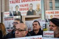 """Protesters hold placards with images of jailed journalists and words which translate as """"You are not alone"""" during a demonstration in front of a courthouse in Istanbul on Christmas Day. Turkey is one of several countries that is restricting press freedoms. Photo: AFP"""