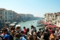 Crowds of tourists pass along the Rialto Bridge over the Grand Canal in Venice. Photo: Alamy