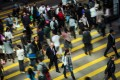 Pedestrians cross a road in the Central district of Hong Kong. The city's share traders have made a brisk start to the year, with stocks closing higher on Wednesday for the seventh session in a row – the longest stretch of gains in more than five months as daily turnover pushed past US$16.63 billion. Photo: Bloomberg