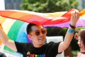 A man holds a rainbow flag after taking part in the Pride Run in Shanghai. The media regulator faces a legal challenge over rules that ban content depicting gay relationships. Photo: AFP