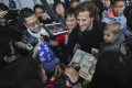 Diego Forlan, carrying his son, Martin, is mobbed by fans as he arrives in Hong Kong. Photos: Edward Wong