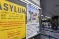 A poster for asylum seekers near the passport control counter of the immigration office at the Narita International airport in Narita. Japan is set to tighten its refugee screening system on Monday. Photo: AFP