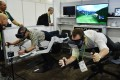 An exhibitor (right) demonstrates the Icaros virtual reality exercise machine at the CES show. Photo: AFP