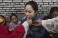 A woman takes communion at a mass at an underground Catholic church near Shijiazhuang, Hebei province. Photo: AFP