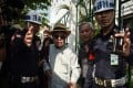 Thai academic and historian Sulak Sivaraksa is escorted by police from the Bangkok Military Court. Photo: AFP