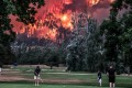 A wildfire burns as golfers play at the Beacon Rock Golf Course in North Bonneville, Washington, on September 4, 2017. Some have blamed a spate of wildfires in North America on climate change, but experts are divided. Photo: Reuters