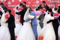 Newlyweds embrace at a collective wedding ceremony in China. A change to the legal definition of joint marital liability, which takes effect on Thursday, is designed to protect spouses from their prodigal partners. Photo: EPA-EFE