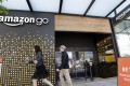People walk past an Amazon Go store in Seattle. Amazon Go shops are convenience stores that don't use cashiers or checkout lines, but use a tracking system that of sensors, algorithms, and cameras to determine what a customer has bought. Photo: AP