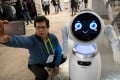 An attendee takes a photo with a robot during the 2018 Consumer Electronics Show in Las Vegas on January 11. Photo: Bloomberg