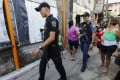 Philippine police walk through a local community as part of the anti-drugs campaign in Quezon City. Photo: EPA