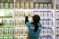 An employee arranges cans of Illuma infant formula, produced by Nestlé, on a shelf at store in Shanghai. Photo: Bloomberg