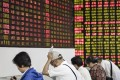 Investors at a securities brokerage in Shanghai. China is speeding up plans to allow trading on domestic bourses of overseas-listed top Chinese tech firms. Photo: Bloomberg