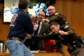 Randall Margraves (left), father of three victims of Larry Nassar, lunges at Nassar (bottom right, in orange jumpsuit behind guards) on Friday. The incident came during the third and final sentencing hearing for Nassar on sexual abuse charges. The charges in this case focus on his work with Twistars, an elite Michigan gymnastics club. Photo: Photo: Reuters