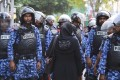 A Maldivian opposition supporter among police during a protest demanding the release of political prisoners in Male. Photo: AP