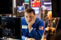 A trader glumly looks at gyrating stocks prices on the floor of the New York Stock Exchange on February 6, 2018. US equity indexes climbed higher after a rocky start, and the benchmark gauge for US share volatility reversed course after hitting a two-year high. Photo: Bloomberg