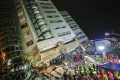Rescuers in Hualien, Taiwan, block off the area outside a building that tilted to one side after its foundations collapsed during Tuesday's 6.4-magnitude earthquake. On Wednesday, almost exactly 24 hours later, the city was struck again by a 5.7-magnitude quake. Photo: AFP