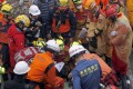 Rescuers from Japan join the search operation on Thursday at an apartment building that collapsed after a strong earthquake in Hualien. Photo: AP