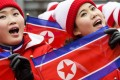 Members of the North Korean delegation wave flags in Pyeongchang. Photo: EPA