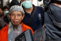 Policemen lead Islamic cleric Aman Abdurrahman to the courtroom for his trial in Jakarta. Photo: Reuters