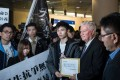 Clayton MacKenzie (second right), a representative of Baptist University, receives a petition letter from a student demonstrator, in Hong Kong on January 26. Hundreds of students protested on the day amid tensions over compulsory testing of Mandarin, the dominant language in mainland China, for graduation. Photo: AFP