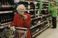 An elderly shopper enjoys a small glass of complementary red wine, as she shops in the drinks aisle of an Asda supermarket in Britain, in this file photo. Photo: Gideon Mendel / Corbis