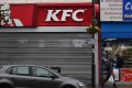 Pedestrians walk past a closed KFC fast food store in south London on February 19. Photo: AFP