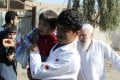 Men carry children away from an explosion site in Lashkar Gah, the capital of the southern Helmand province, in Afghanistan on Saturday. Photo: AP