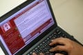 A programmer shows a sample of a ransomware cyberattack on a laptop. Photo: EPA/RITCHIE B. TONGO