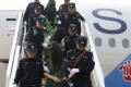 Extradited mainland Chinese and Taiwanese suspects involved in wire fraud are escorted off a plane at Beijing international airport in April 2016. Photo: Associated Press