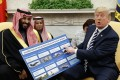 US President Donald Trump shows a chart highlighting arms sales to Saudi Arabia during a meeting with Saudi Crown Prince Mohammed bin Salman in the Oval Office of the White House on Tuesday. Photo: AP