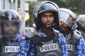 Police stand guard during a protest demanding the release of political prisoners in Male, Maldives. Photo: AP