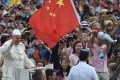 A file picture of Pope Francis waving to the crowd as he passes a person holding a Chinese flag during his weekly general audience in St Peter's Square two years ago. Photo: AFP